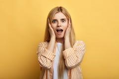 De emotionele mooie blonde handen van de vrouwenholding op haar wangen royalty-vrije stock fotografie