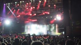 De energieke menigte die van ventilators bij muziekfestival springen, geïmponeerd door rotsster toont stock videobeelden