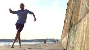 De energieke Mens danst Disco op een Riverbank met een Hoge Steenmuur in slo-Mo stock videobeelden