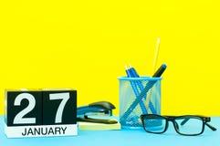 27 de enero Día 27 del mes de enero, calendario en fondo amarillo con los materiales de oficina Flor en la nieve Fotos de archivo libres de regalías