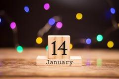 14 de enero Día 14 del mes, calendario en fondo de madera Flor en la nieve imagen de archivo