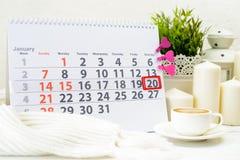 20 de enero Día 20 de mes en el calendario blanco, cerca de una taza de c Imagenes de archivo