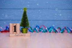 1 de enero día 1 de sistema de enero en calendario de madera en fondo de madera azul del tablón Imagen de archivo libre de regalías