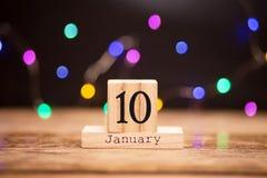 10 de enero Día 10 de sistema de enero en calendario de madera en fondo oscuro con el bokeh de la guirnalda Flor en la nieve Comp foto de archivo