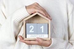 21 de enero en el calendario la muchacha está sosteniendo un calendario de madera Día internacional de abrazo Foto de archivo