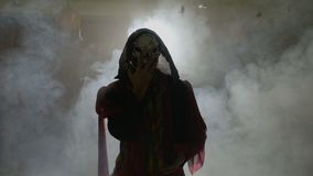 De enge acteur kleedde zich in een angstaanjagend Halloween-kostuum die griezelige bewegingen met handen doen - stock videobeelden