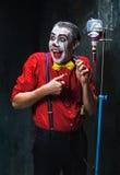 De enge clown en de druppel met bloed op dackachtergrond Het concept van Halloween Royalty-vrije Stock Afbeeldingen