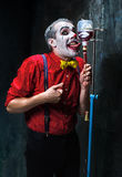 De enge clown en de druppel met bloed op dackachtergrond Het concept van Halloween Stock Foto