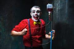 De enge clown en de druppel met bloed op dackachtergrond Het concept van Halloween Royalty-vrije Stock Fotografie