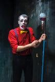 De enge clown en de druppel met bloed op dackachtergrond Het concept van Halloween Stock Fotografie