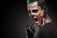 De enge die zombiemake-up bemant gezicht op zwarte achtergrond wordt geïsoleerd Royalty-vrije Stock Foto's