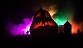 De enge mening van Halloween-pompoen met zombieën bij begraafplaats draagt de kerk en de griezelige bewolkte hemel met mist, het  Stock Afbeeldingen