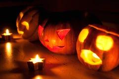 De enge de pompoen en de meloen hefboom-o-lantaarns van Halloween op zwarte achtergrond staken met kleine ronde en sterkaarsen aa Royalty-vrije Stock Foto