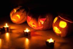 De enge de pompoen en de meloen hefboom-o-lantaarns van Halloween op zwarte achtergrond staken met kleine ronde en sterkaarsen aa Royalty-vrije Stock Fotografie