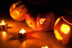 De enge de pompoen en de meloen hefboom-o-lantaarns van Halloween op zwarte achtergrond staken met kleine ronde en sterkaarsen aa Stock Afbeeldingen