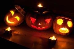 De enge de pompoen en de meloen hefboom-o-lantaarns van Halloween op zwarte achtergrond staken met kleine ronde en sterkaarsen aa Stock Fotografie