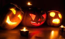 De enge de pompoen en de meloen hefboom-o-lantaarns van Halloween op zwarte achtergrond staken met kleine ronde en sterkaarsen aa Royalty-vrije Stock Afbeeldingen