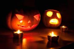 De enge de pompoen en de meloen hefboom-o-lantaarns van Halloween op zwarte achtergrond staken met kleine ronde en sterkaarsen aa Stock Foto