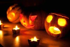 De enge de pompoen en de meloen hefboom-o-lantaarns van Halloween op zwarte achtergrond staken met kleine ronde en sterkaarsen aa Royalty-vrije Stock Foto's