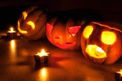 De enge de pompoen en de meloen hefboom-o-lantaarns van Halloween op zwarte achtergrond staken met kleine ronde en sterkaarsen aa Stock Afbeelding