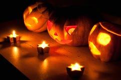 De enge de pompoen en de meloen hefboom-o-lantaarns van Halloween op zwarte achtergrond staken met kleine ronde en sterkaarsen aa Royalty-vrije Stock Afbeelding