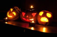 De enge de pompoen en de meloen hefboom-o-lantaarns van Halloween op zwarte achtergrond staken met kleine ronde en sterkaarsen aa Stock Foto's