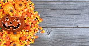 De enge pompoen van Halloween met traktaties die linkergrens op weath vormen royalty-vrije stock fotografie