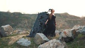 De engel van dood verzamelt zich met krachten om oorlog, meisje in zwarte lange uitstekende kleding met kantkokers alleen naast g stock footage