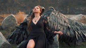 De engel van dood verzamelt zich met krachten om oorlog, meisje in zwarte lange uitstekende kleding met kantkokers alleen naast g stock videobeelden