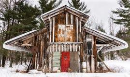 De Engel van de zaagmolenwinter builing behandeld in deuren van sneeuw de heldere coloerd royalty-vrije stock afbeelding