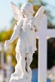 De engelenstandbeeld dat van het kind in een kruis leunt Royalty-vrije Stock Fotografie