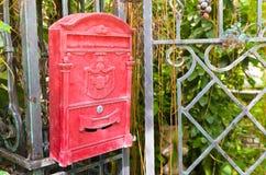 De Engelse rode brievenbus hangt op poort Stock Afbeeldingen
