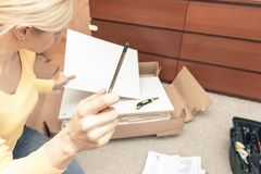 De enige jonge vrouw het assembleren stukken van nieuw meubilair en het lezen van de instructie, open dozen met meubilairdetails  stock afbeeldingen