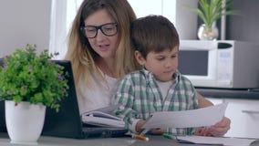 De enige moeder werkt thuis aan computer die op telefoon spreken en zoon behandelen stock videobeelden