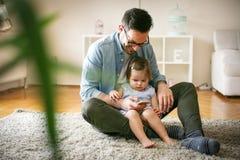De enige vader weet zijn dochter gebruikend slimme telefoon Stock Afbeelding