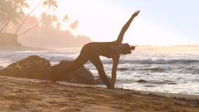De enorme rek die van het meisjessilhouet yoga op zand doen stock video