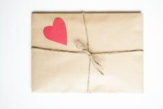 De envelop van kraftpapier met rood hart Stock Afbeelding