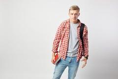De ernstige blonde kerel met zwarte rugzak op zijn schouder gekleed in een witte t-shirt, een rode geruite overhemd en jeans houd royalty-vrije stock fotografie