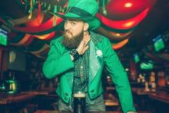 De ernstige en gekke jonge mens in St Patrick kostuumtribune in bar en kijkt op camera Hij houdt hand dicht bij hals Agressief stock foto's