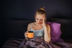 De ernstige en ongerust gemaakte jonge vrouw zit op bed Zij houdt kop thee met citroen en houdt hand op voorhoofd Zij heeft stock fotografie
