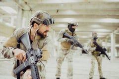 De ernstige en sterke moordenaar bevindt zich met andere twee militairen in brengt en snakt ruimte en het kijken aan het recht zi Stock Foto's