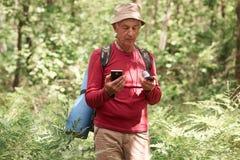 De ernstige enthousiaste mens die in bos, het houden wandelen omringt en smartphone in zijn handen, kiezend zijn reisroute, die z stock foto's