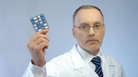 De ernstige in hand pillen van de artsenholding, adviserend efficiënt medicijn stock afbeeldingen