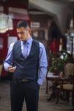 De ernstige jonge man in een vest en met uren Royalty-vrije Stock Afbeelding