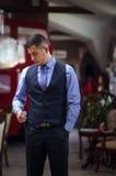 De ernstige jonge man in een vest en met uren Stock Foto