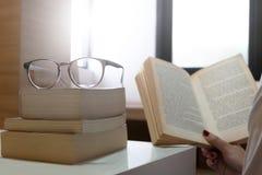 De ernstige jonge student die een boek in een bibliotheek lezen selecteerde nadruk Stock Foto's