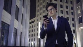 De ernstige jonge zakenman met een smartphone en hoofdtelefoons loopt in een nachtstad stock footage