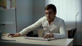 De ernstige jonge zakenmanwerken aangaande Desktop Toevallige mens die computer in bureau met behulp van stock footage