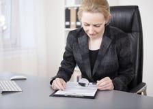 De ernstige Lezing van de Bureauvrouw met Vergrootglas stock afbeelding
