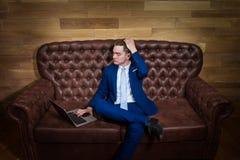 De ernstige mens in kostuum werkt met laptop thuis bureau royalty-vrije stock foto